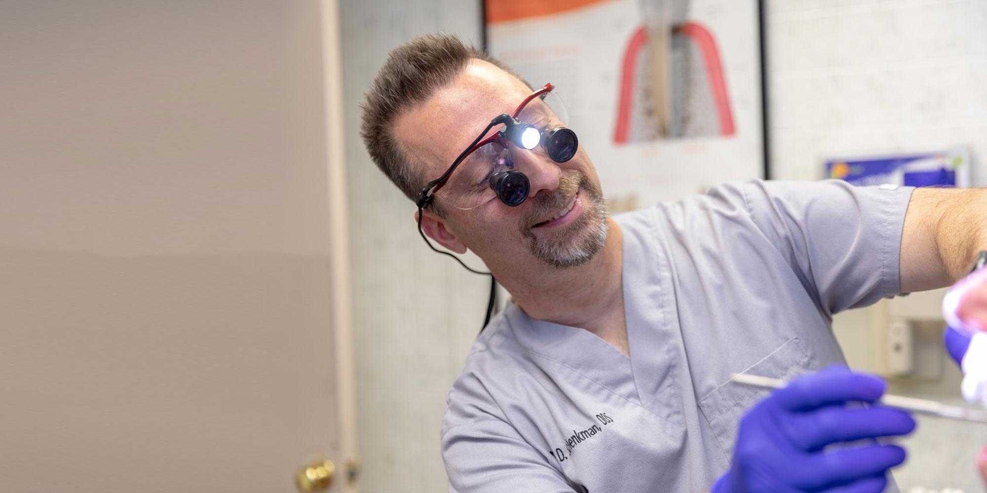 dr schenkman performing dental procedure